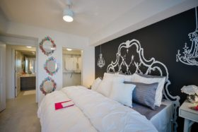 Bedroom with plush bedding, large walk-in closet and adjacent bathroom